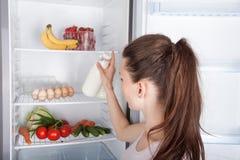 Επιλεγμένο γυναίκα γάλα στο ανοιγμένο ψυγείο στοκ φωτογραφία με δικαίωμα ελεύθερης χρήσης