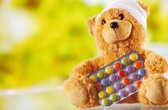 Επιδεμένο Teddy αντέχει με συσκευασμένα τα φύλλο αλουμινίου χάπια Στοκ Φωτογραφίες