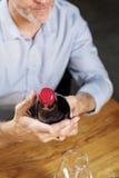 Επιλογή κρασιού Άτομο που διαβάζει μια ετικέτα σε ένα μπουκάλι στοκ φωτογραφία