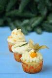 Επιλογή τριών cupcakes σε ένα μπλε ξύλινο υπόβαθρο Στοκ Εικόνες