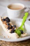 Επιδόρπιο μπανανών με το granola, τα οργανικά βακκίνια και τη φρέσκια μέντα σε ένα άσπρο πιάτο με το ανοικτό πράσινο κουτάλι Στοκ φωτογραφία με δικαίωμα ελεύθερης χρήσης