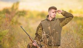 Εποχές κυνηγιού και παγίδευσης Το άτομο βάναυσο το υπόβαθρο φύσης εκτροφέων θηραμάτων Άδεια κυνηγιού Γενειοφόρος σοβαρός κυνηγός στοκ εικόνες