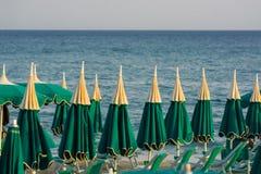 Εποχή διακοπών - πολλές ομπρέλες παραλιών στο ηλιοβασίλεμα παραλιών θάλασσας Στοκ Εικόνες