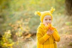 Εποχή πτώσης και έννοια ανθρώπων Το μικρό κορίτσι σε ένα κίτρινα πλεκτά παλτό και ένα καπέλο έχει τη διασκέδαση στο πάρκο φθινοπώ στοκ εικόνες
