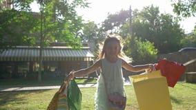 Εποχή των εκπτώσεων, χαρούμενο παιδί αγοραστών με τις αγορές στα τρεξίματα χεριών κατά μήκος του πράσινου χορτοτάπητα στο φωτεινό απόθεμα βίντεο