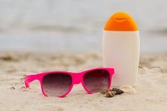 Εποχιακή έννοια, κοχύλια, ρόδινα γυαλιά ηλίου και λοσιόν ήλιων Στοκ Φωτογραφία