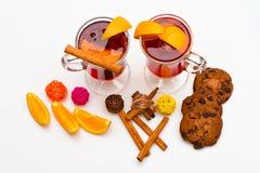 Εποχιακή έννοια ποτών Τα γυαλιά με το θερμαμένο κρασί ή το ποτό κοντά στα juicy πορτοκαλιά φρούτα στο άσπρο υπόβαθρο, κλείνουν επ Στοκ Εικόνες