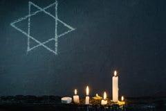 Επτά καίγοντας κεριά και το αστέρι του Δαυίδ ενάντια στοκ φωτογραφία