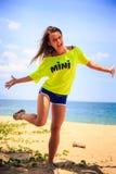 λεπτό κορίτσι στα γέλια μπλουζών λεμονιών στην παραλία ενάντια στη θάλασσα Στοκ εικόνα με δικαίωμα ελεύθερης χρήσης