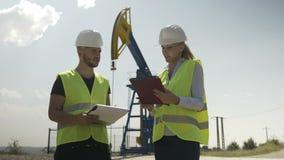 Επόπτες βιομηχανίας πετρελαίου που ελέγχουν τη λειτουργία της μονάδας αντλιών πετρελαίου - απόθεμα βίντεο