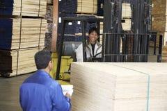 Επόπτης από Laborer με Forklift το φέρνοντας ξύλο στοκ φωτογραφία