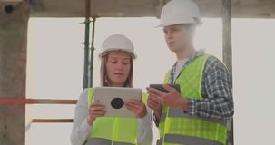 Επόπτης ενός κτηρίου κάτω από τον άνδρα οικοδόμησης που συζητά με τη γυναίκα σχεδιαστών μηχανικών την πρόοδο της οικοδόμησης και απόθεμα βίντεο