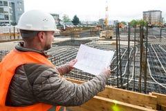 Επόπτης κατασκευής με το σχέδιο για την περιοχή Στοκ Εικόνες