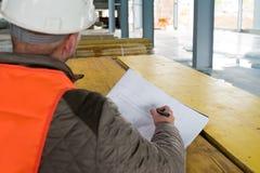 Επόπτης κατασκευής με το σχέδιο για την περιοχή Στοκ εικόνες με δικαίωμα ελεύθερης χρήσης
