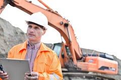 Επόπτης που κοιτάζει μακριά κρατώντας την περιοχή αποκομμάτων στο εργοτάξιο οικοδομής Στοκ Φωτογραφίες
