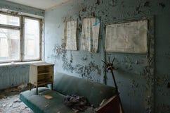 Ερήμωση στο δωμάτιο του νοσοκομείου, απολύτως εγκαταλειμμένη πόλη-φάντασμα Pripyat στη ζώνη αλλοτρίωσης πυρηνικού σταθμού του Τσέ στοκ φωτογραφία