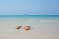 Εραστές που βρίσκονται στο landwash σε μια παραλία γενναιοδωρίας Στοκ Φωτογραφία