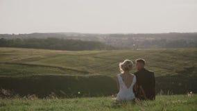 Εραστές σε έναν τομέα στο ηλιοβασίλεμα, νέος τύπος που αγκαλιάζει τη φίλη του στο ηλιοβασίλεμα, που κάθεται σε έναν λόφο φιλμ μικρού μήκους