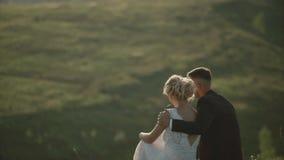 Εραστές σε έναν τομέα στο ηλιοβασίλεμα, νέος τύπος που αγκαλιάζει τη φίλη του στο ηλιοβασίλεμα, που κάθεται σε έναν λόφο απόθεμα βίντεο