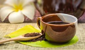 Εραστής καφέ Το φλυτζάνι καφέ στο πράσινο φύλλο με τον ψημένο καφέ επιζητά επάνω Στοκ Εικόνες