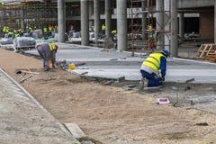 Εργάτες οικοδομών που βάζουν τις πέτρες επίστρωσης Στοκ Εικόνες