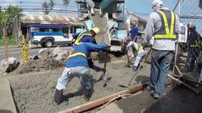 Εργάτες οικοδομών που μαζεύουν με τη τσουγκράνα το υγρό τσιμέντο απόθεμα βίντεο