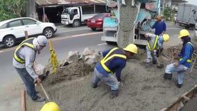 Εργάτες οικοδομών που μαζεύουν με τη τσουγκράνα το υγρό τσιμέντο φιλμ μικρού μήκους