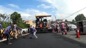 Εργάτες οικοδομών που στρώνουν την άσφαλτο στη γέφυρα απόθεμα βίντεο