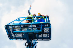 Εργάτες οικοδομών για την περιοχή στην υδραυλική ανυψωτική κεκλιμένη ράμπα Στοκ εικόνες με δικαίωμα ελεύθερης χρήσης