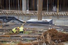 Εργάτες οικοδομών που επιλέγουν και που μετρούν τις ράβδους σιδήρου Στοκ Εικόνες