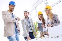 Εργάτες οικοδομών που ελέγχουν τα αρχιτεκτονικά σχέδια Στοκ εικόνα με δικαίωμα ελεύθερης χρήσης