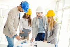 Εργάτες οικοδομών που ελέγχουν τα αρχιτεκτονικά σχέδια Στοκ Εικόνες