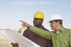 Εργάτες οικοδομών που διαβάζουν τα σχεδιαγράμματα Στοκ Εικόνες