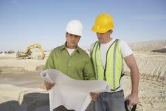 Εργάτες οικοδομών που διαβάζουν τα σχεδιαγράμματα Στοκ Φωτογραφία