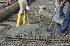 Εργάτες οικοδομών που πετούν τη συγκεκριμένη χρησιμοποιώντας συγκεκριμένη μάνικα Στοκ εικόνα με δικαίωμα ελεύθερης χρήσης