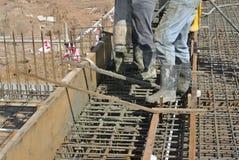 Εργάτες οικοδομών που πετούν τη συγκεκριμένη χρησιμοποιώντας συγκεκριμένη μάνικα Στοκ Φωτογραφίες