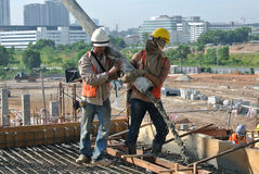 Εργάτες οικοδομών που πετούν τη συγκεκριμένη χρησιμοποιώντας συγκεκριμένη μάνικα Στοκ Εικόνα
