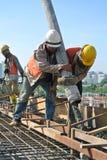 Εργάτες οικοδομών που πετούν τη συγκεκριμένη χρησιμοποιώντας συγκεκριμένη μάνικα Στοκ Φωτογραφία
