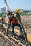 Εργάτες οικοδομών που πετούν τη συγκεκριμένη χρησιμοποιώντας συγκεκριμένη μάνικα Στοκ εικόνες με δικαίωμα ελεύθερης χρήσης