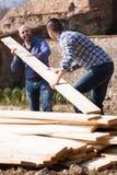 Εργάτες που τακτοποιούν την ξυλεία οικοδόμησης στο αγρόκτημα Στοκ φωτογραφίες με δικαίωμα ελεύθερης χρήσης