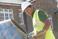 Εργάτης οικοδομών που αναμιγνύει το τσιμέντο Στοκ Εικόνα