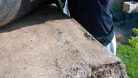 Εργάτης οικοδομών που αφαιρεί το υλικό κατασκευής σκεπής αισθητό από μια έχουσα διαρροή σάπια στέγη απόθεμα βίντεο
