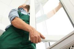 Εργάτης οικοδομών που εγκαθιστά το νέο παράθυρο στοκ εικόνες