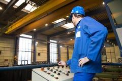 Εργάτης οικοδομών που ενεργοποιεί μια μηχανή Στοκ Εικόνες