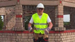 0 εργάτης οικοδομών που μιλά και που παρουσιάζει αντίχειρα κάτω απόθεμα βίντεο