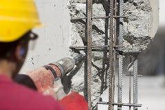 Εργάτης οικοδομών που χρησιμοποιεί ένα τρυπώντας με τρυπάνι εργαλείο δύναμης Στοκ Εικόνες
