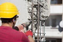 Εργάτης οικοδομών που χρησιμοποιεί ένα τρυπώντας με τρυπάνι εργαλείο δύναμης Στοκ Φωτογραφία