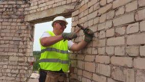 Εργάτης οικοδομών που χρησιμοποιεί το σφυρί και τη σμίλη απόθεμα βίντεο