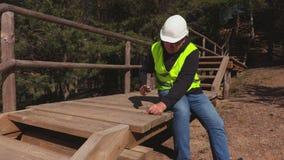Εργάτης οικοδομών που χρησιμοποιεί το σφυρί στα ξύλινα σκαλοπάτια απόθεμα βίντεο