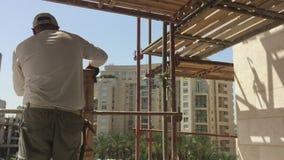 Εργάτης οικοδομών για ένα ικρίωμα απόθεμα βίντεο